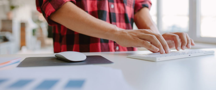 man with clean hands typing on a keyboard with a mac mouse on the side